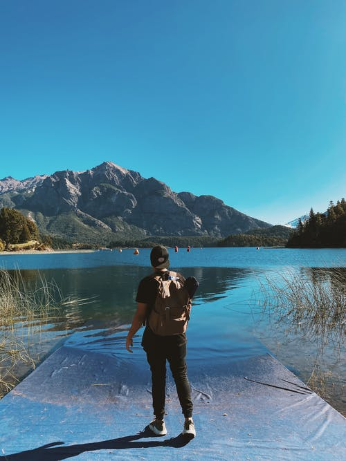 Full body back view of unrecognizable male hiker with backpack admiring rippling water of pond surrounded by mountains