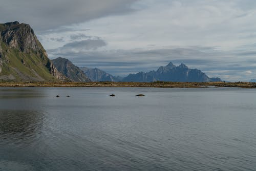 Mountains located near calm water in daylight