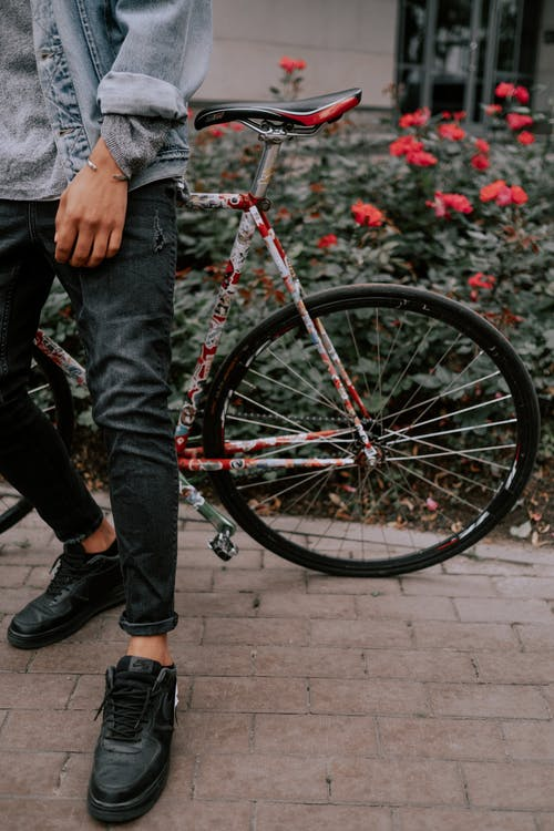 Person in Blue Denim Jacket and Blue Denim Jeans Standing Beside Black and Red Mountain Bike