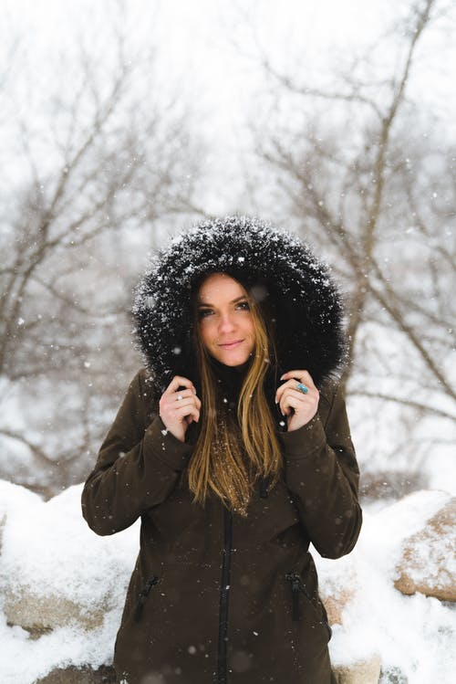 Cheerful young woman in warm clothes standing in winter forest and looking at camera in soft daylight