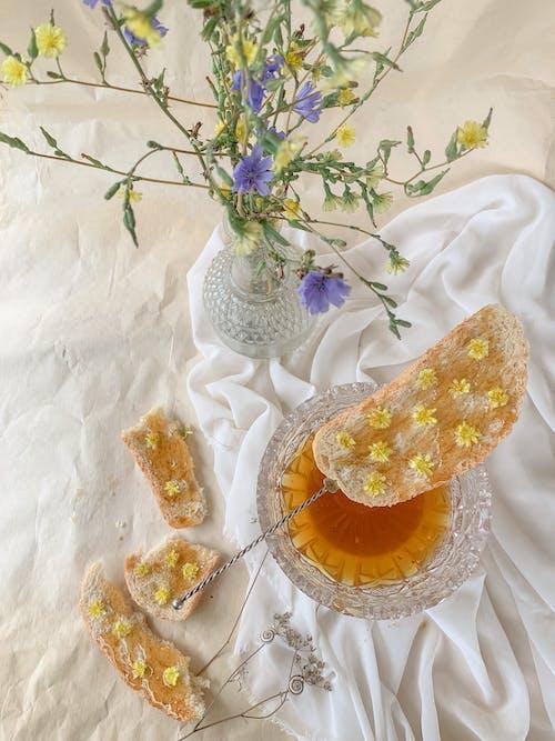 Хлеб с медом возле вазы с цветами