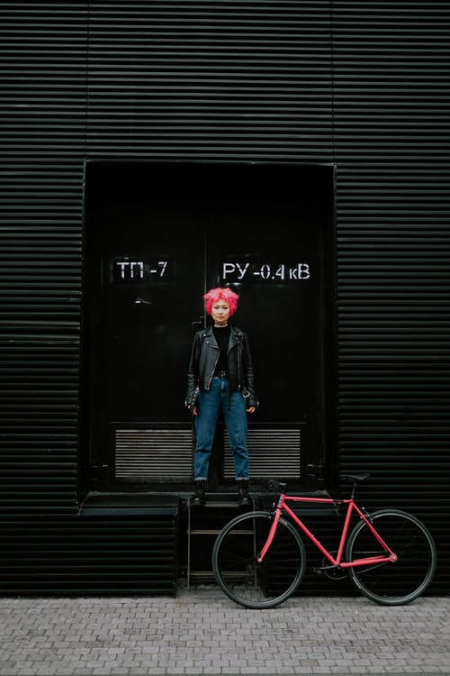 Man in Blue Denim Jacket Standing in Front of Black Wall