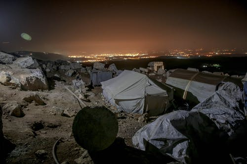 Tents for homeless people in stony terrain at night