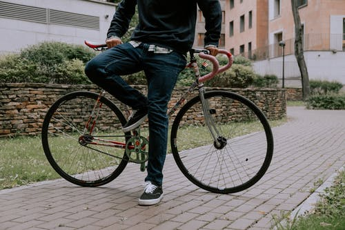 Person in Blue Denim Jeans and Black Jacket Riding on Pink Bicycle
