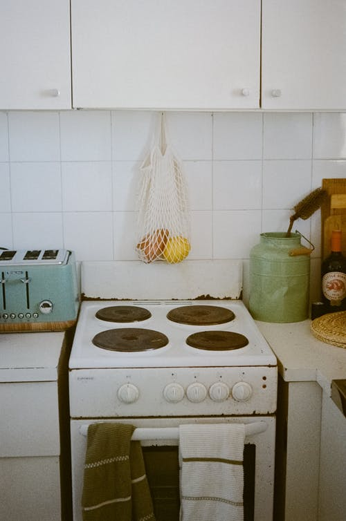 Interior of cozy kitchen with aged cooking stove and cupboard in bright daylight