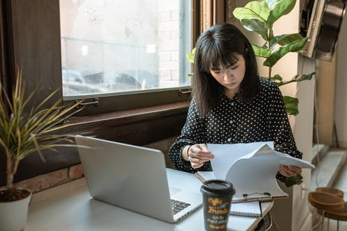 Woman in Black and White Long Sleeve Shirt Looking On A Paperwork