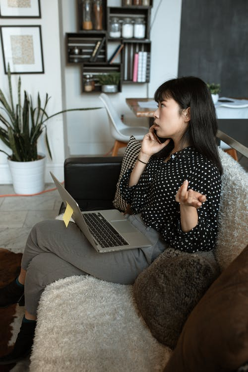 Woman Sitting On A Black Couch Using Cellphone