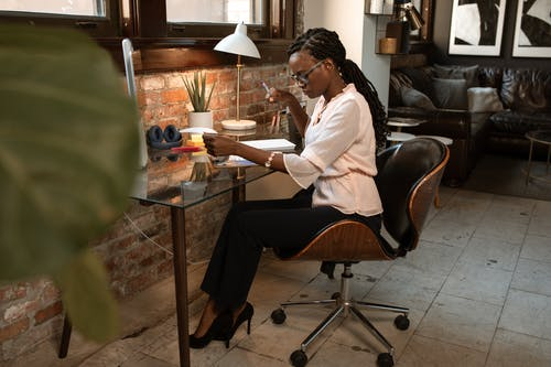 Businesswoman Sitting on Black Leather Chair Looking Over Some Paperwork