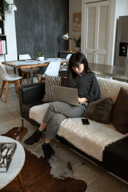 黑色和白色的圓點長袖襯衫,坐在棕色的沙發椅子上的女人