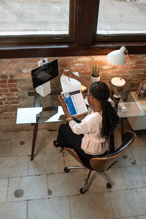 Frau Im Weißen Langarmhemd, Das Auf Dem Braunen Stuhl Lesebuch Sitzt