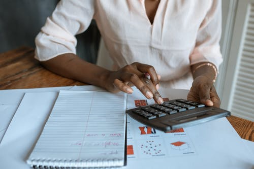 Persona En Camisa De Vestir Blanca Con Una Calculadora