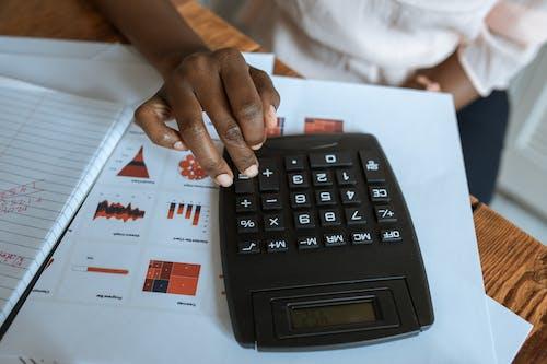 Person Using Black Desk Calculator