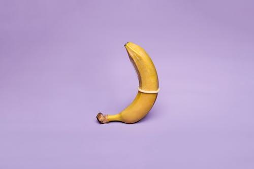 Yellow Banana on Purple Background
