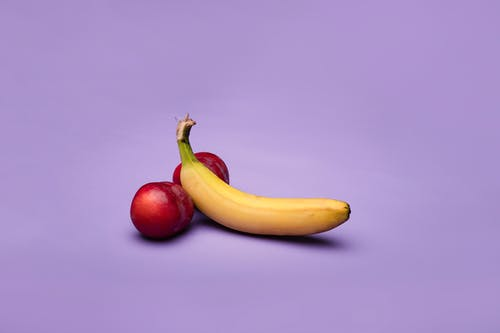 Yellow Banana Fruit and Peaches On Purple Background