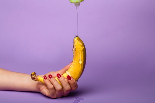 Person Holding Yellow Banana With Syrup