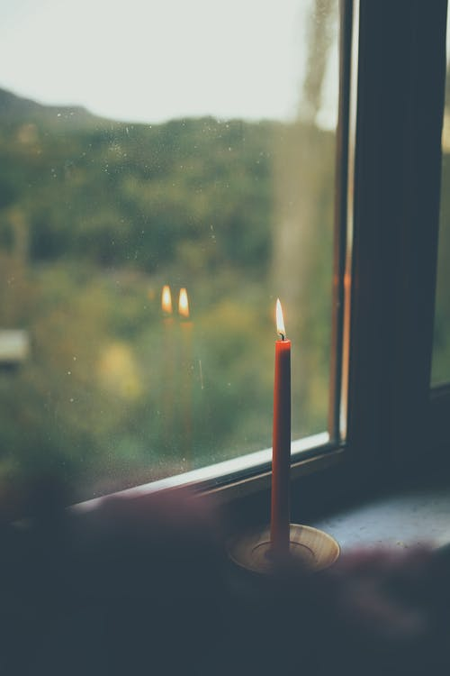 Burning candle reflecting in window at home