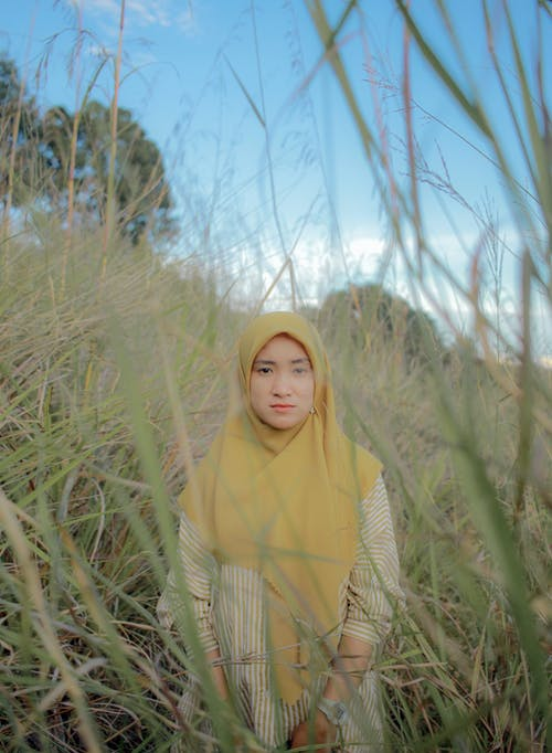 Woman in Green Hijab Standing on Green Grass Field