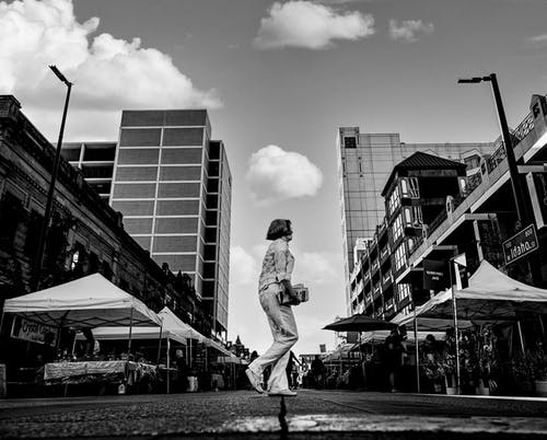 Black and white of anonymous female near street tents and tall buildings under cloudy sky
