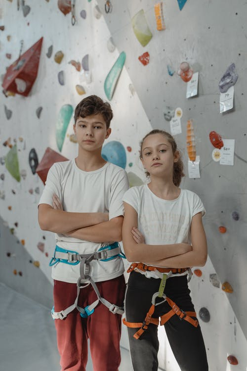 Young Man and A Girl Wearing Harness Standing Beside A Rock Wall