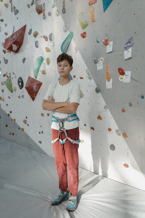 A Young Man Wearing Harness Standing Near A Rock Wall