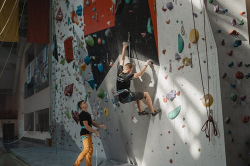 Man in Black T-shirt and Blue Denim Jeans Doing Wall Climbing