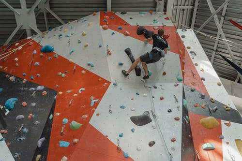 Man in Black T-shirt and Black Shorts Climbing on Red and White Concrete Wall during