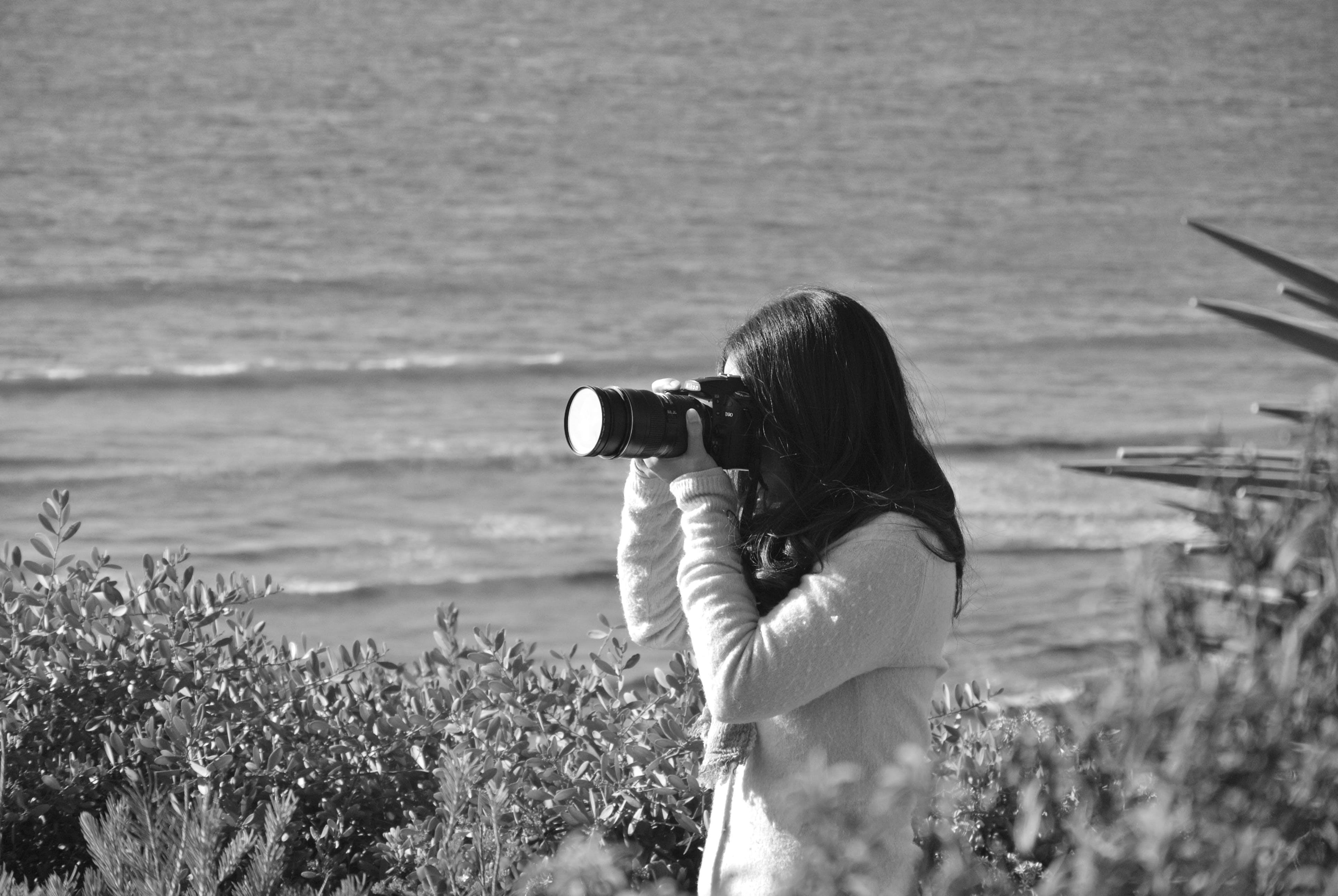 Grayscale Photograph of a Woman Using Dslr Camera
