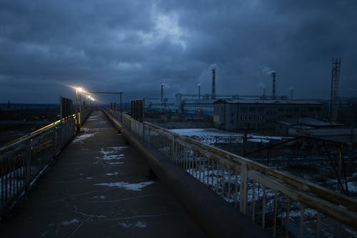 Long bridge with bright luminous streetlamps across railway tracks under gloomy cloudy sky in dusk