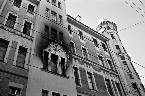 Black and white of exterior of aged residential building with dirty windows and walls after fire placed in city in daytime