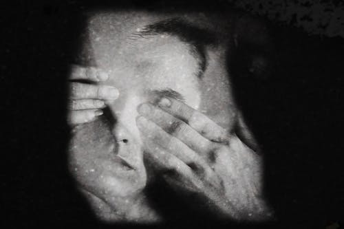 Black and white of anonymous serious person covering eyes with hands against black background