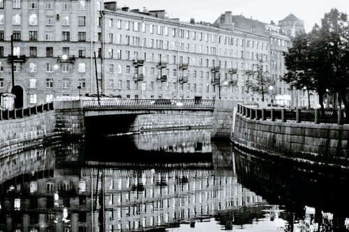 Black and white of residential buildings placed near calm river channel in city in daytime