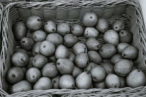 From above of black and white pile of fresh pears in whicker basket placed on stall in local grocery market
