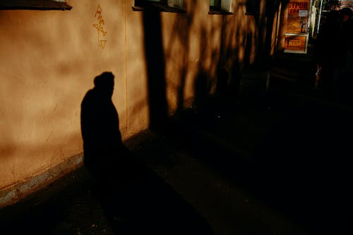 Unrecognizable person shadow on old building wall with entrance door in town at night