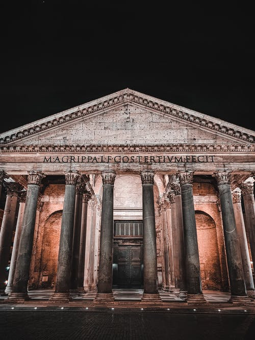 Low angle of Pantheon with marble columns with glowing lights on facade against dark night sky in Rome