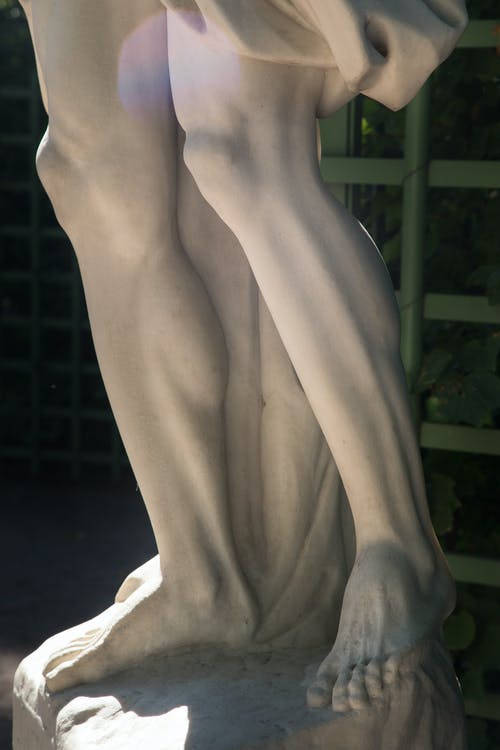 Detail of ancient sculpture with carved muscles on pedestal in Summer Garden in Saint Petersburg