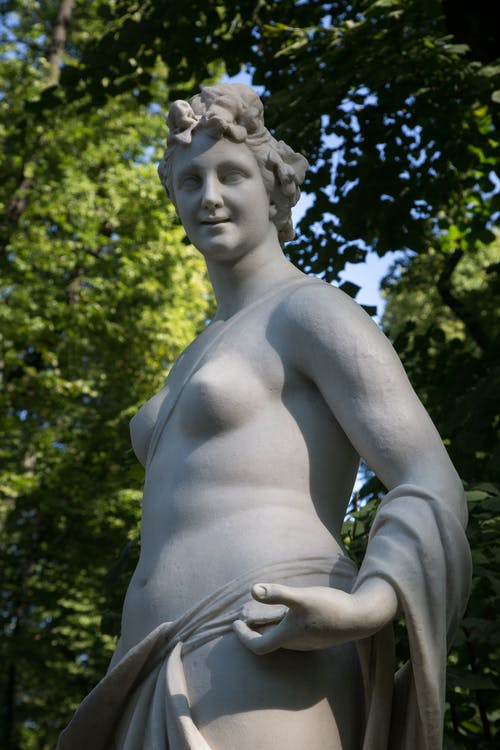 Low angle of marble sculpture of Thalia Greek mythology muse against green trees in Summer Garden in Saint Petersburg