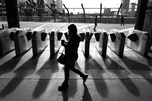 Black and white side view of faceless female in casual wear walking near pay gates and drinking coffee