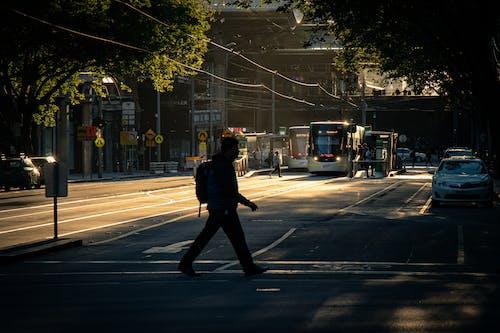 Unrecognizable man crossing road in city