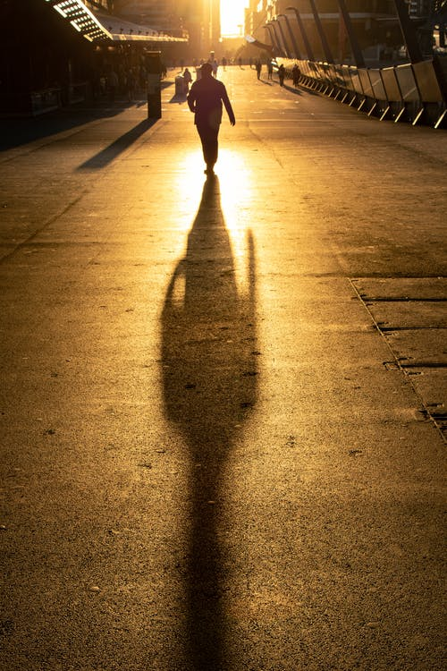 Back view of anonymous person in casual outfit walking along asphalt walkway in evening at sundown