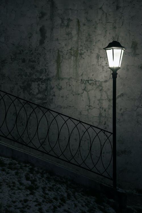 Luminous streetlight with metal fence in dark avenue