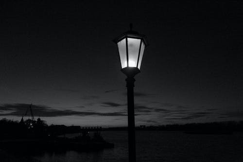 Black and white of vintage metal street lamp near river under dusky cloudy sky in evening
