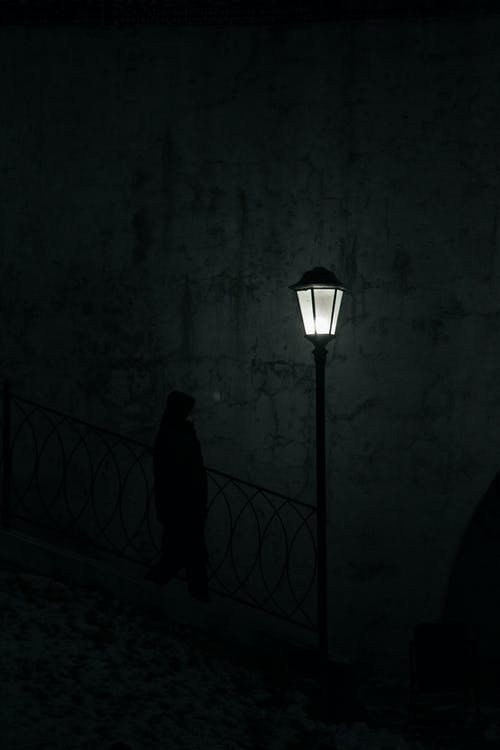 Side view of anonymous male walking down on urban steps with luminous street lamp in dark evening