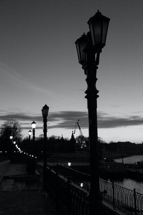 Black and white of evening pier with old streetlights and calm river under cloudy sky