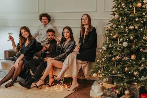 Friends Sitting On A Sofa Beside A Christmas Tree