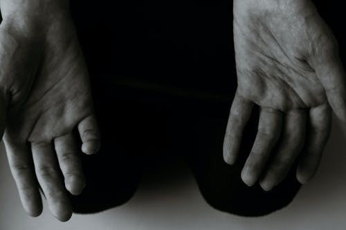 From above black and white of crop anonymous person showing lines on palms of hands