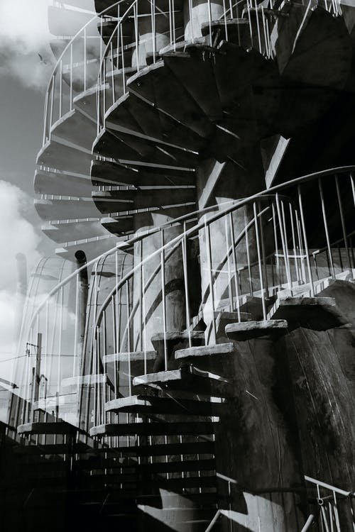Black and white double exposure of tall stone spiral stairway with metal railings and pillar located on street in city