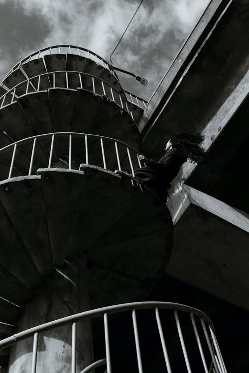 Black and white from below of concrete spiral staircase with metal handrails located near cement structure on street in city