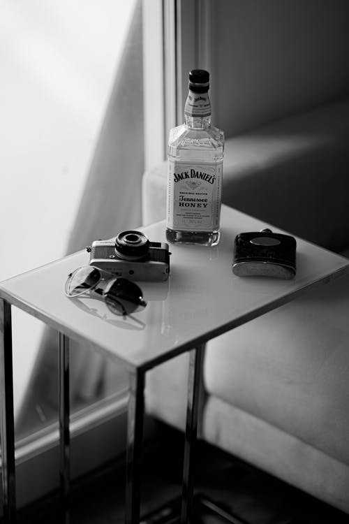 Bottle of whiskey on table with photo camera