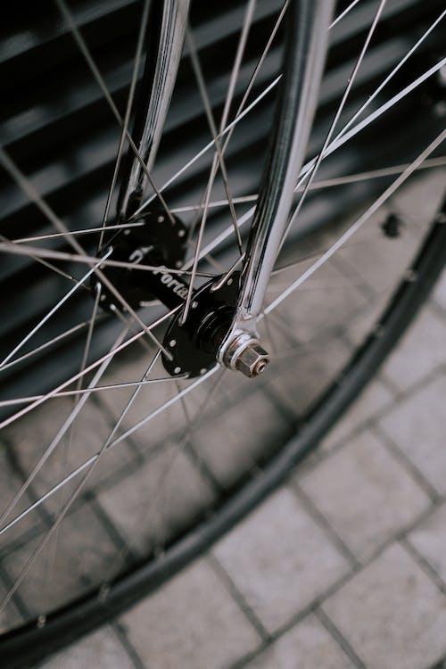 Black Bicycle Wheel on Brown Brick Floor