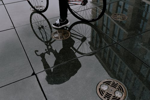 Person in Black Pants Standing on Black and White Bicycle